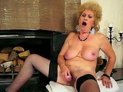 Breasty grandma Effie shoves a new dildo in her shaved pussy in front of the fireplace